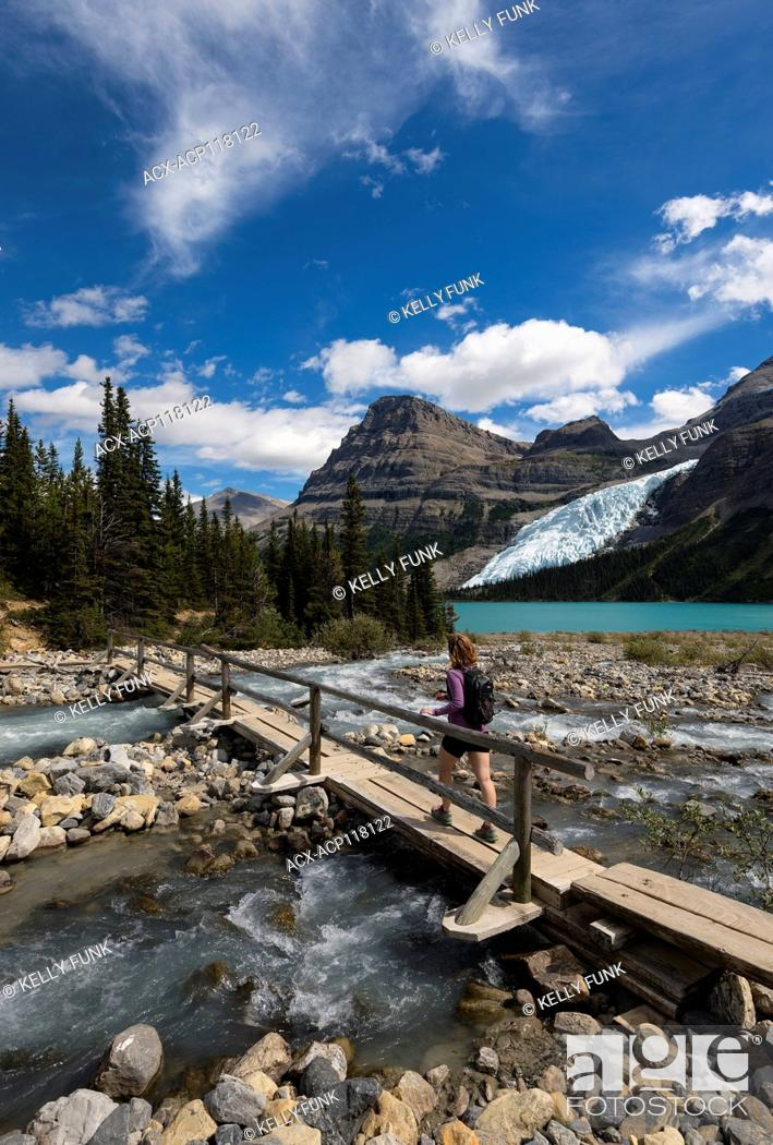 Imagen: A young woman hikers over the Robson river on the Berg lake trail, with the Robson glacier and Rearguard mountain in the background, Mt.