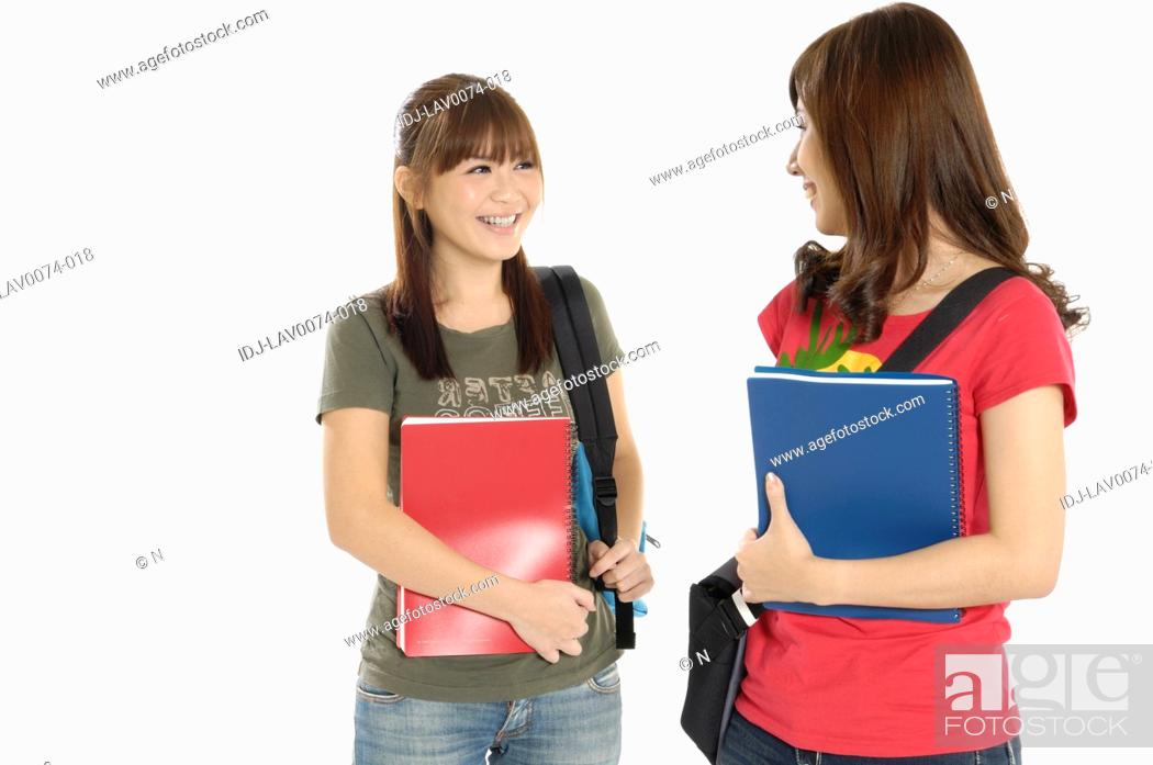 Stock Photo: Female university students smiling at each other.
