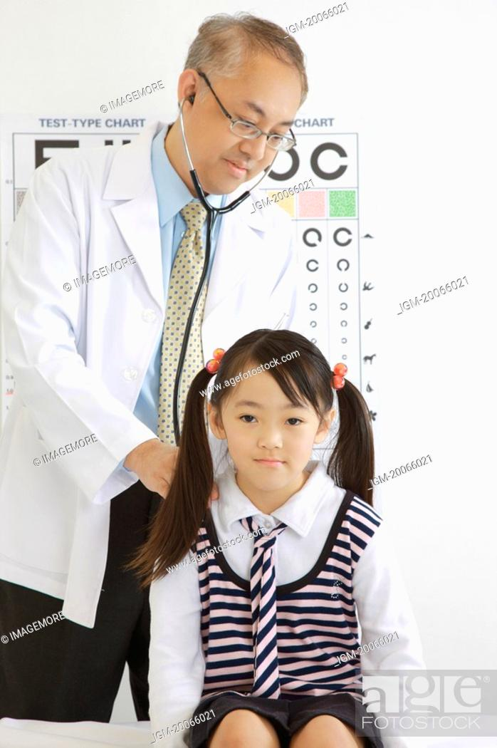 Stock Photo: Doctor wearing stethoscope and checking for the little girl.