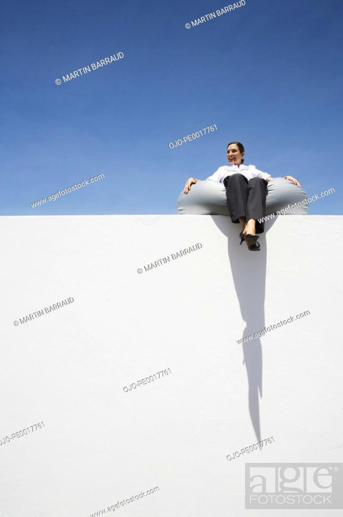 Stock Photo: Businesswoman sitting on beanbag chair on wall outdoors.
