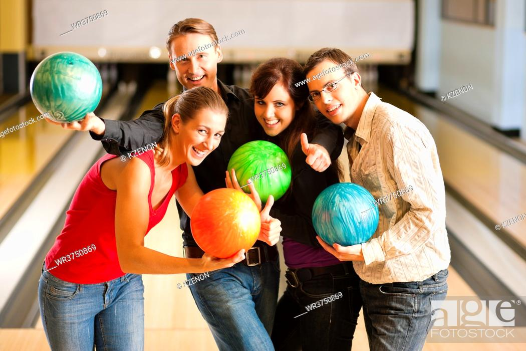 Imagen: Group of four friends in a bowling alley having fun, holding their bowling balls.