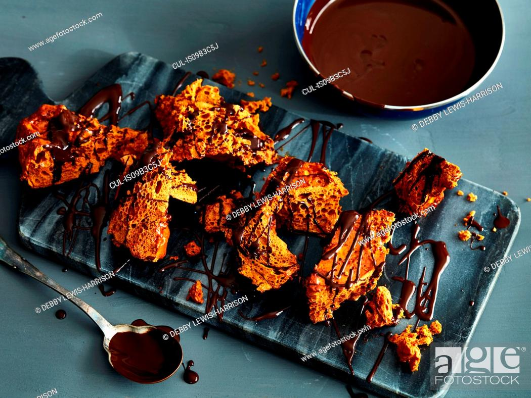 Stock Photo: Broken honeycomb toffee with melted chocolate garnish on marble cutting board.