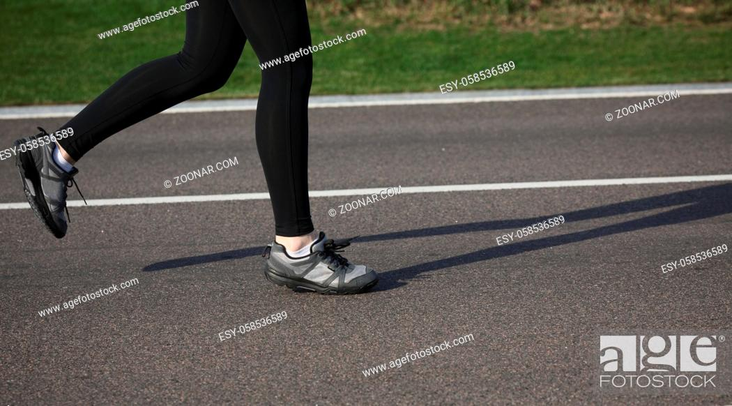 Photo de stock: Shallow depth of field, toned with instagram like filter, flare effect. Closeup of female in running shoes going for run on road at sunrise or sunset.