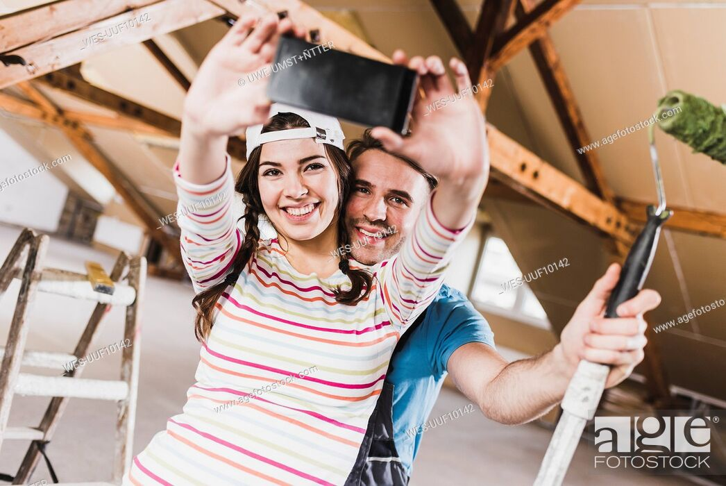 Stock Photo: Young couple renovating their new home, taking smart phone selfies.
