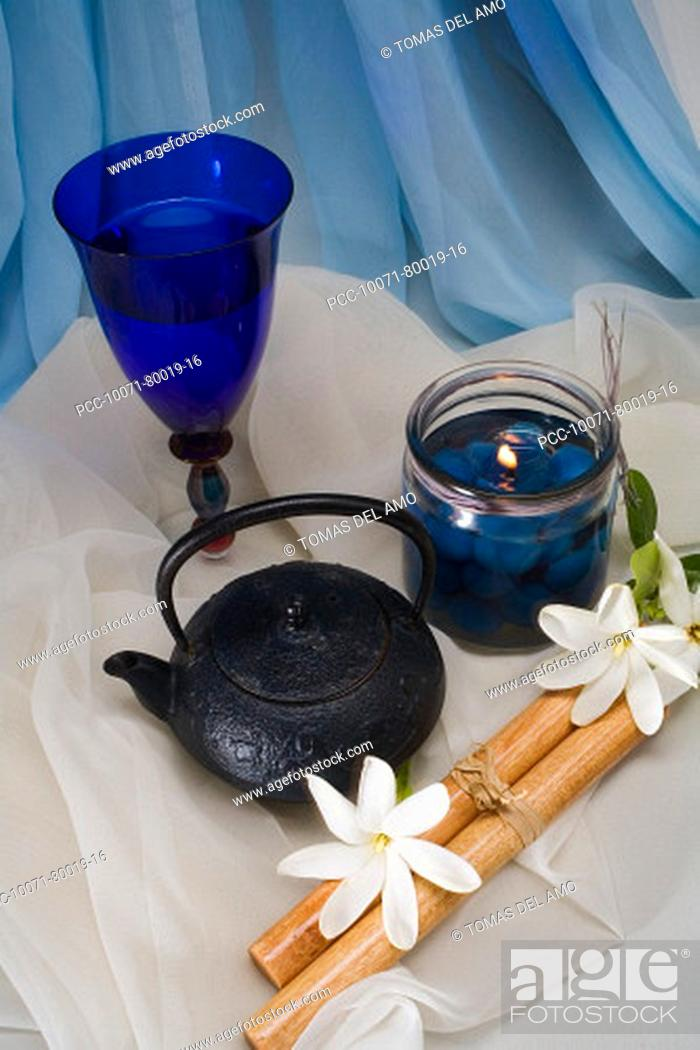 Imagen: Spa elements, candle, flowers, kettle and glass nestled upon flowing cloth.