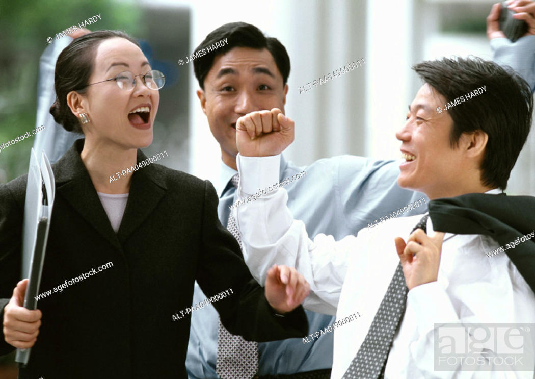 Stock Photo: Two men and a woman smiling, outside.