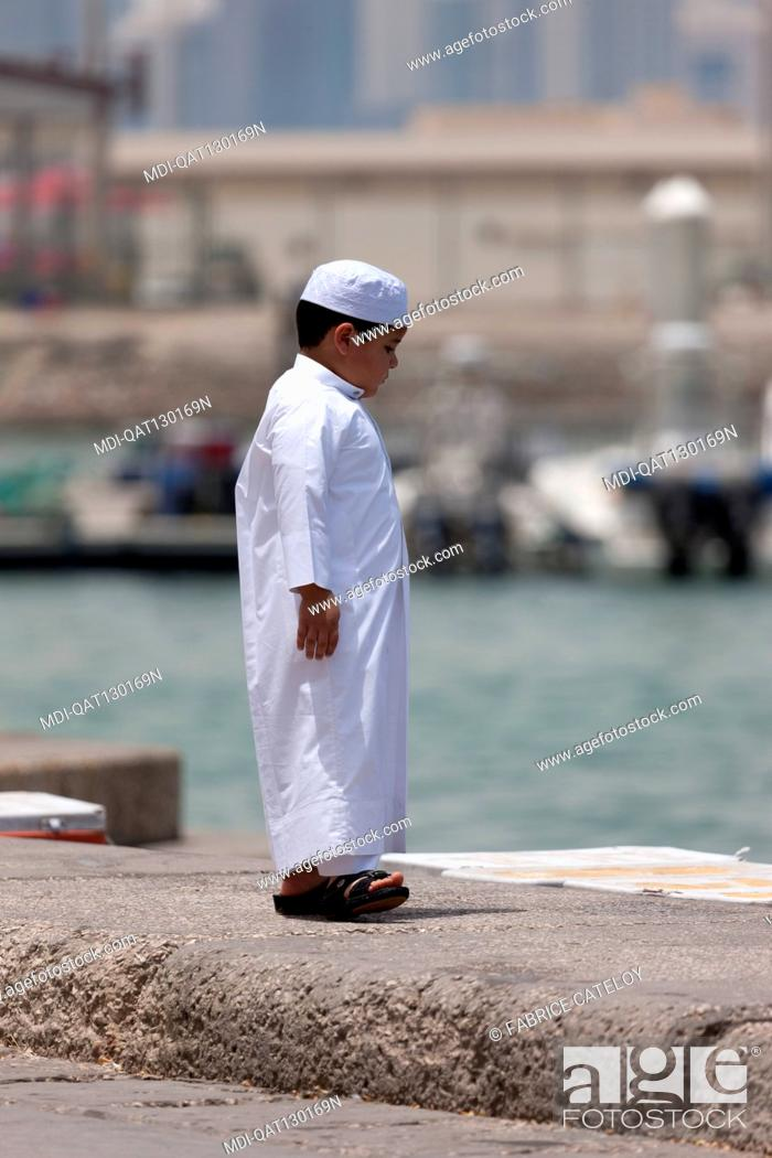 Imagen: Qatar - Doha - Fish market on the corniche - Young Qatari boy looking fresh fishes into ice boxes.