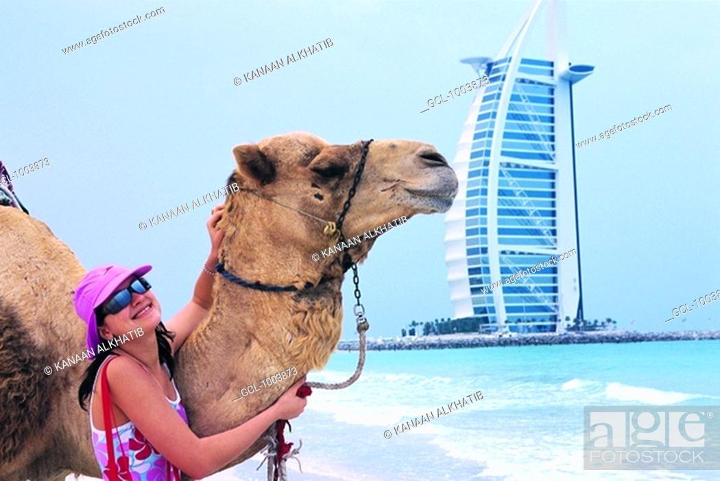 Stock Photo: Western tourist touching a camel on the beach in Dubai, UAE.