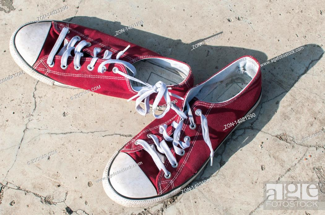 Stock Photo: Pair of worn out vintage red old canvas sneakers on outside concrete surface.
