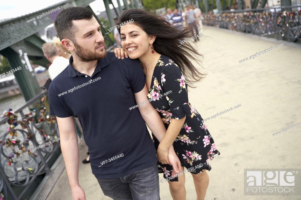 Imagen: Young couple walking on bridge. Eisener Steg, Frankfurt am Main, Germany.