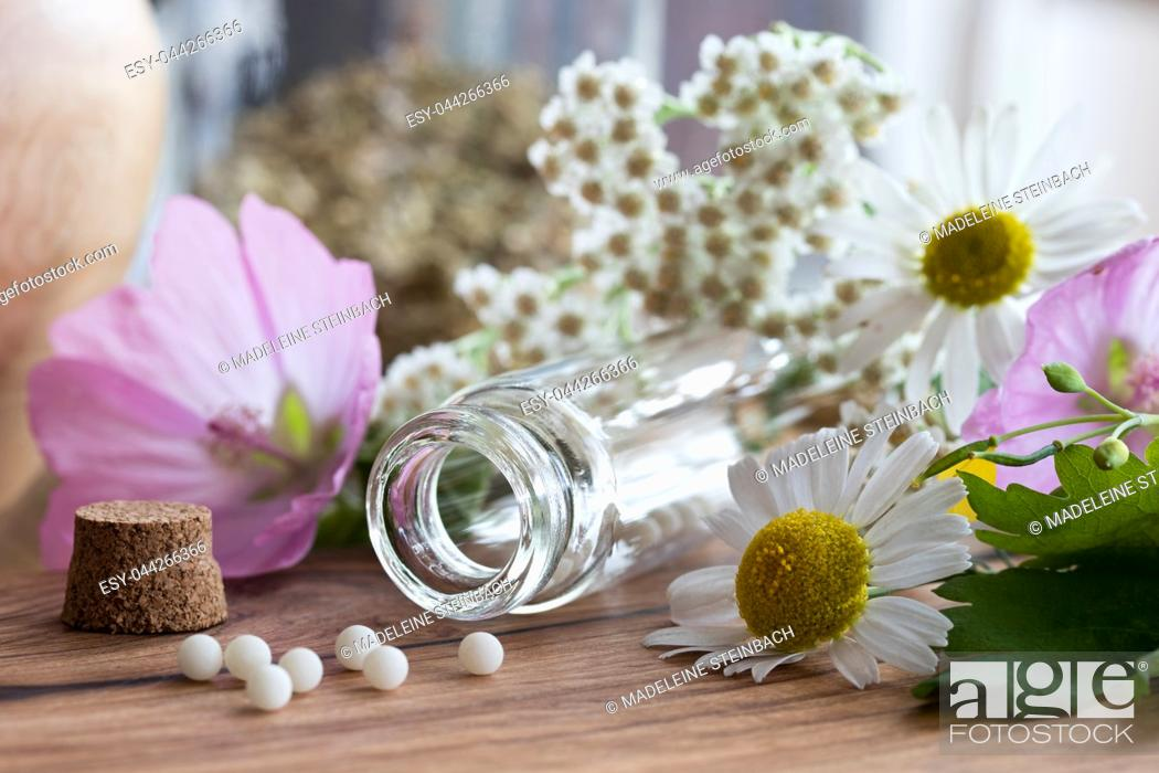 Stock Photo: A bottle of homeopathic globules with chamomile, yarrow and other flowers in the background.
