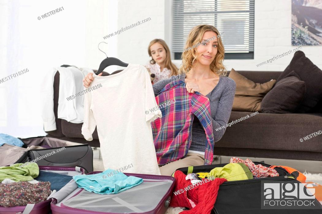 Stock Photo: Germany, Leipzig, Mother and daughter packing suitcase for vacation.