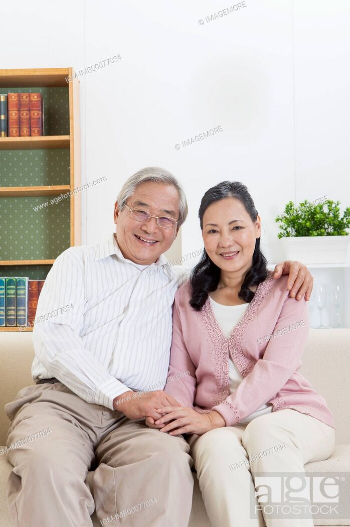 Imagen: Senior couple holding hands and smiling at the camera together,.