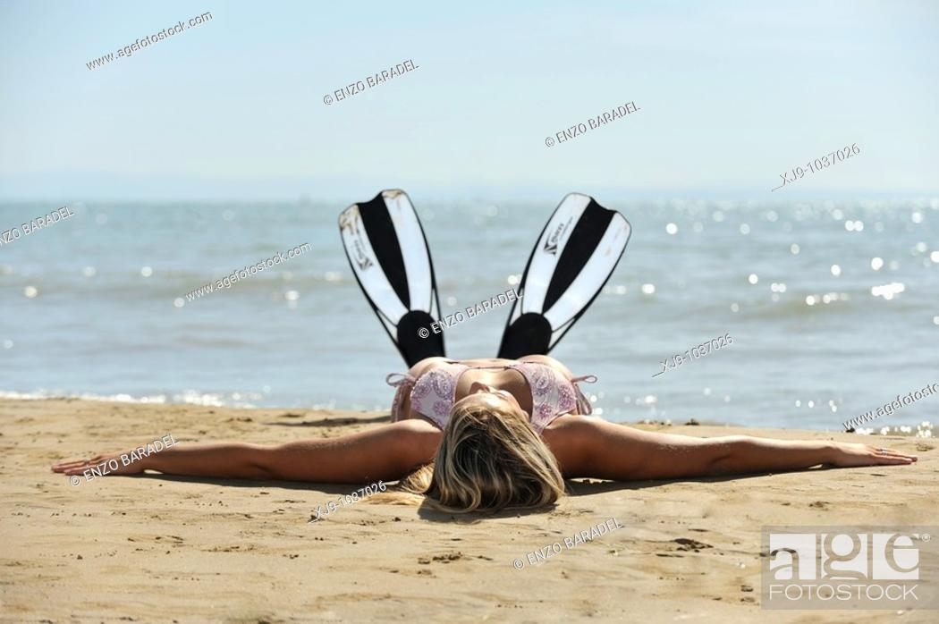 Stock Photo: Girl with diving fins lying on the beach.