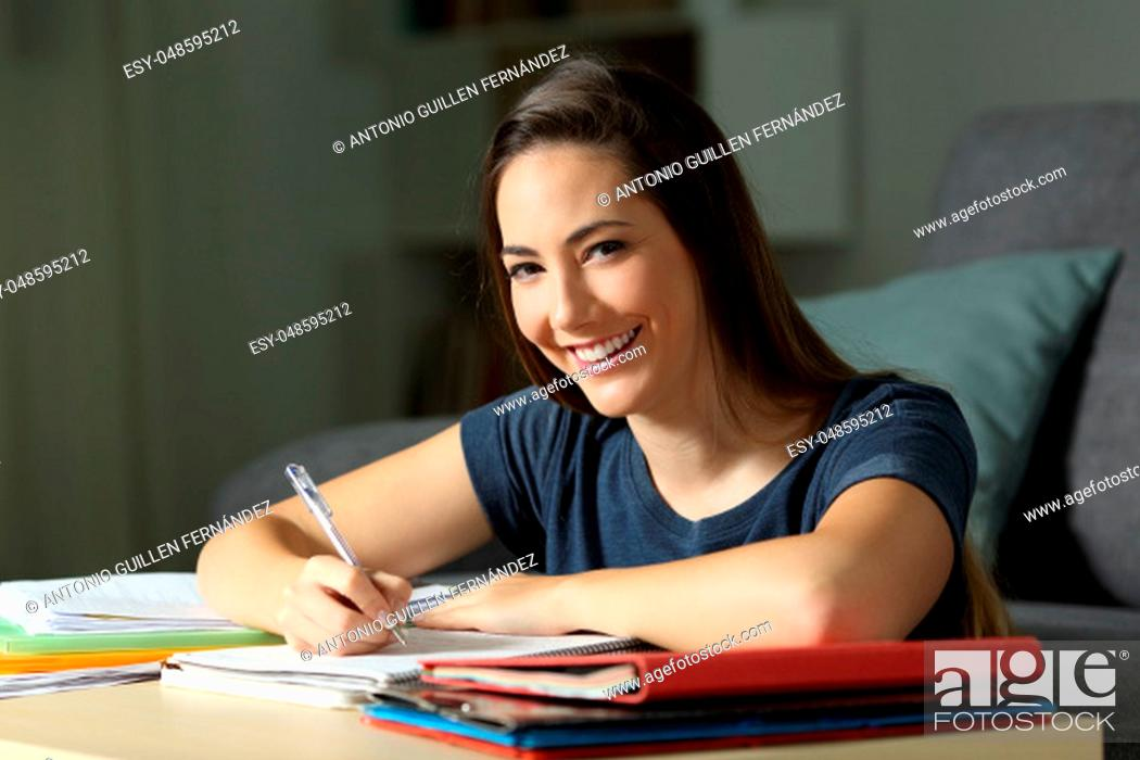 Stock Photo: Happy student studying late hours in the night looking at you at home.