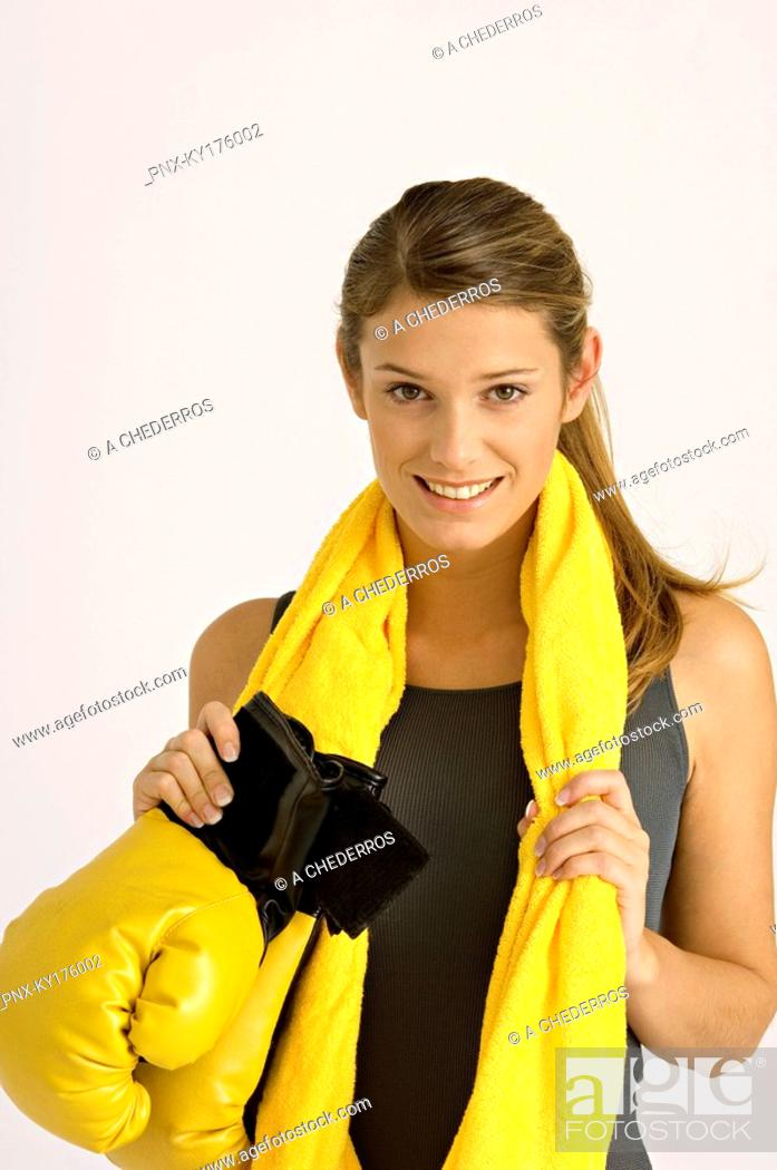 Stock Photo: Portrait of a female boxer holding boxing gloves and smiling.