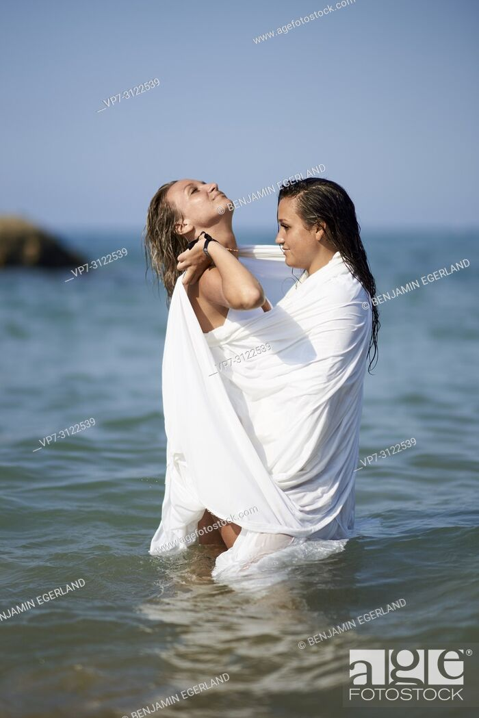 Stock Photo: two women shrouded in white blanket sheet, standing in sea, best friends, looking at each other, holiday. Chersonissos, Crete, Greece.