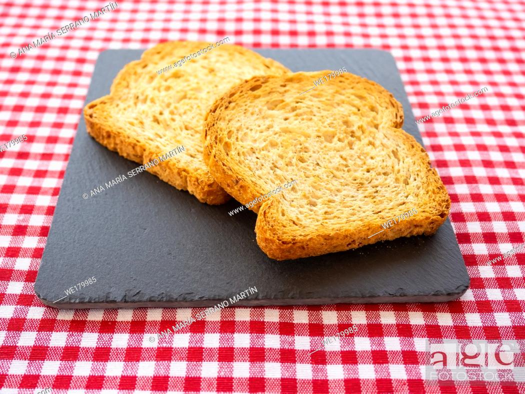 Imagen: Two slices of toast on a slate plate and tablecloth vintage style.