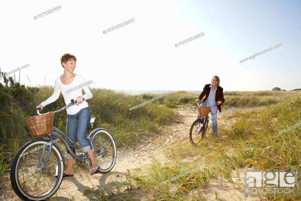 Stock Photo: Couple cycling in field.