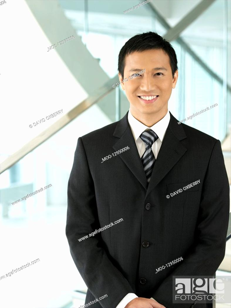 Stock Photo: Confident Businessman standing hands clasped.