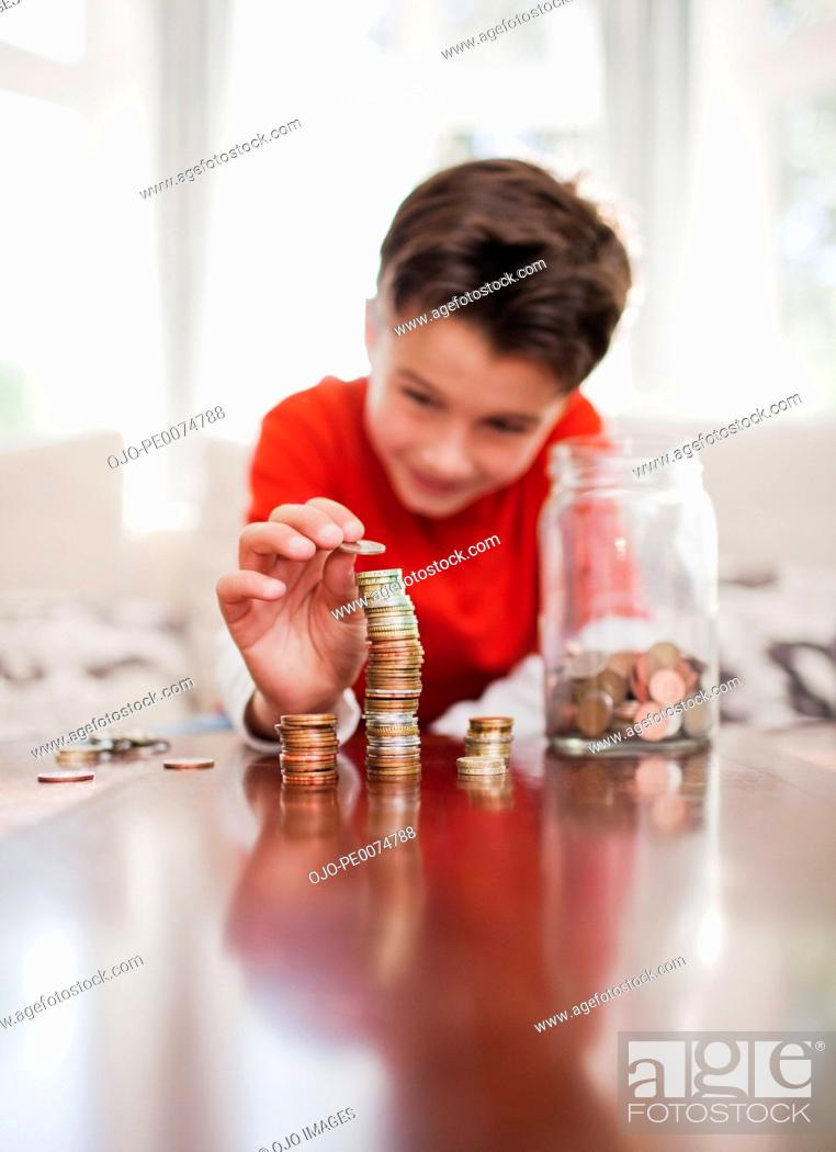 Stock Photo: Boy stacking coins.