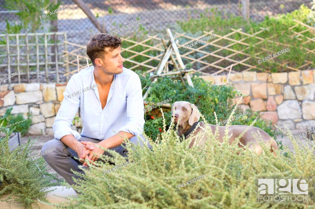 Stock Photo: Contemplative man with a dog in garden.