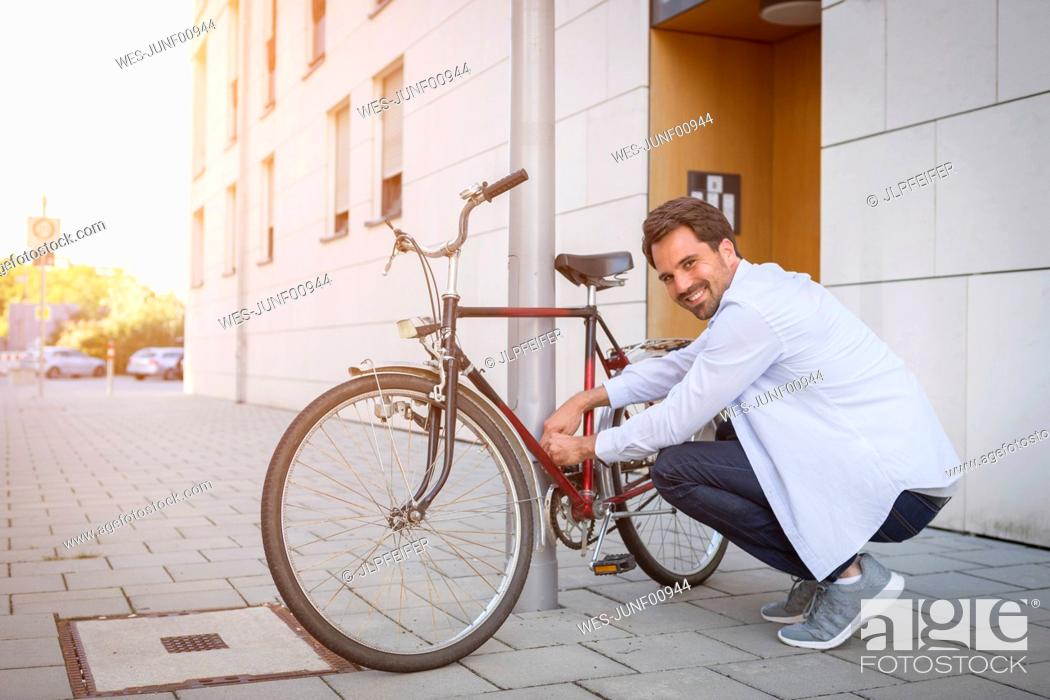 Photo de stock: Man locking his bicycle to a lamp post.