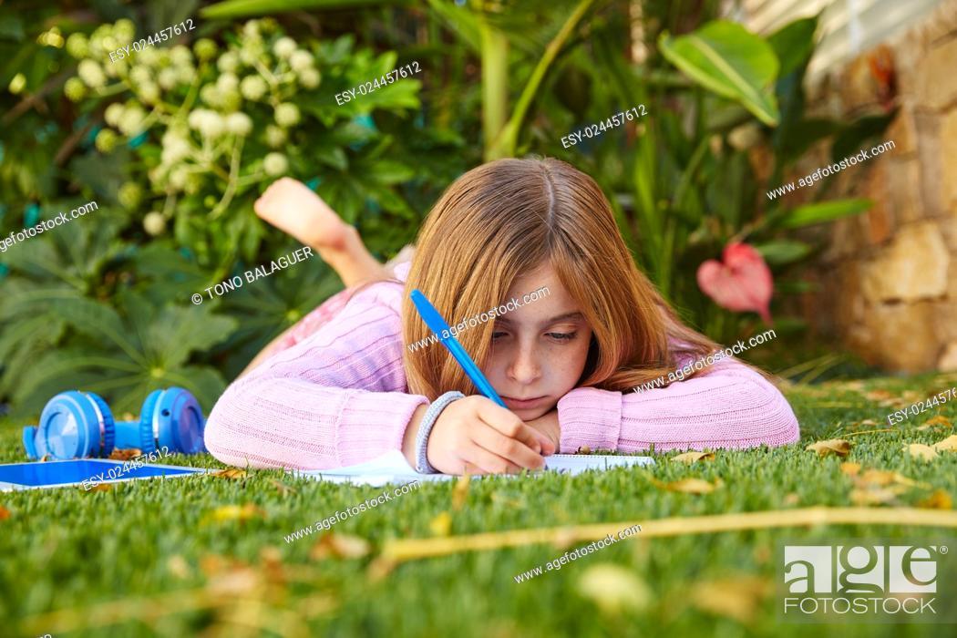 Stock Photo: Blond kid girl homework lying on grass turf writting notebook.