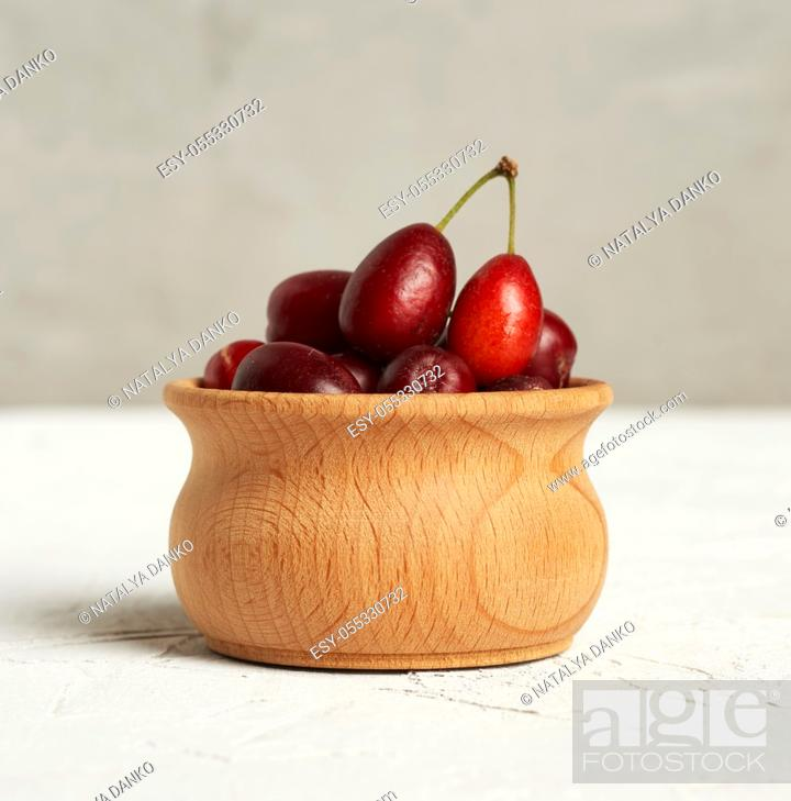 Stock Photo: ripe red dogwood berries in a wooden bowl, gray background, close up.