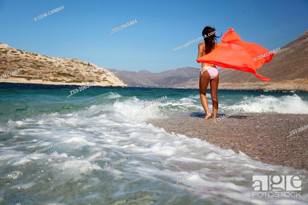 Stock Photo: Woman in bikini walking towards the waves at the beach, Amorgos, Cyclades Islands, Greek Islands, Greece, Europe.