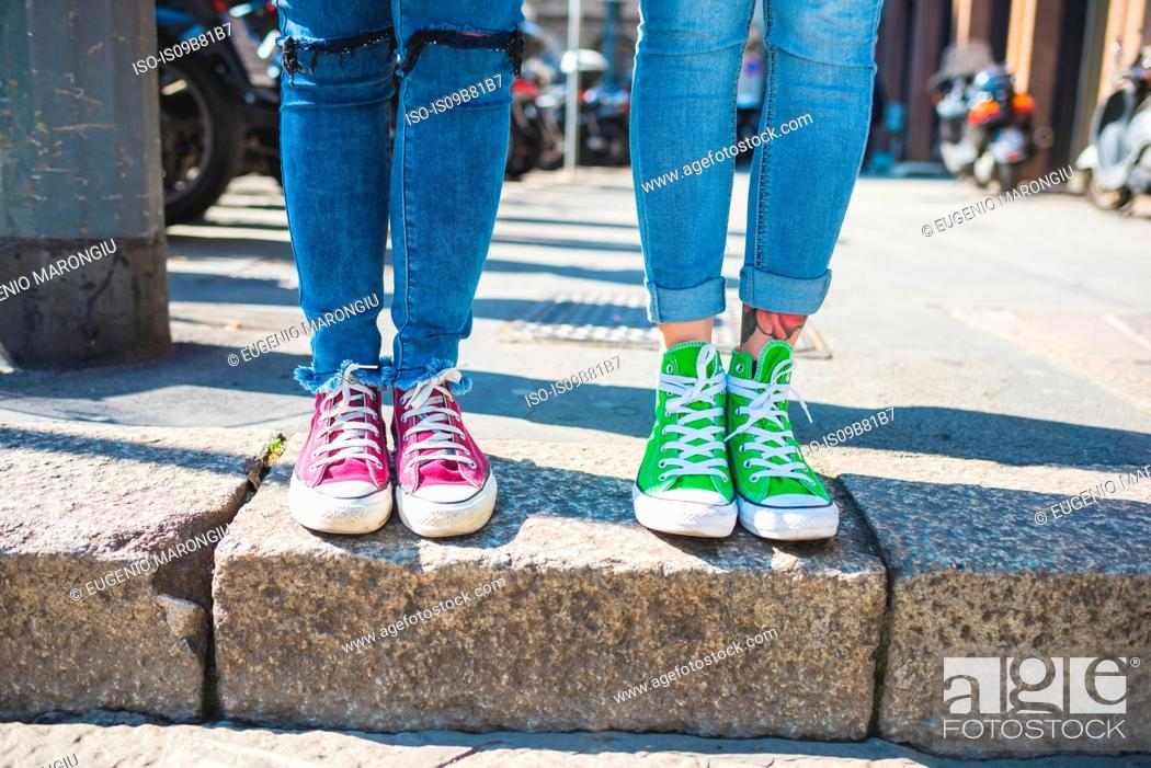 Stock Photo: Women's feet in trainers on step, Milan, Italy.
