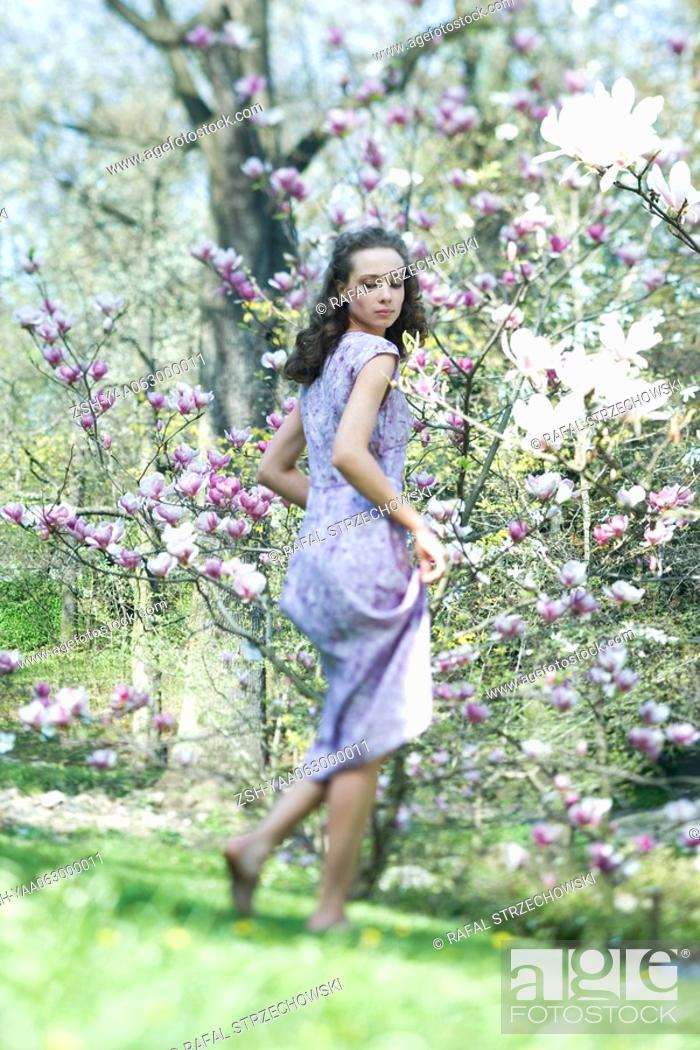 Stock Photo: Young woman in dress walking in meadow, looking over shoulder, low angle view.