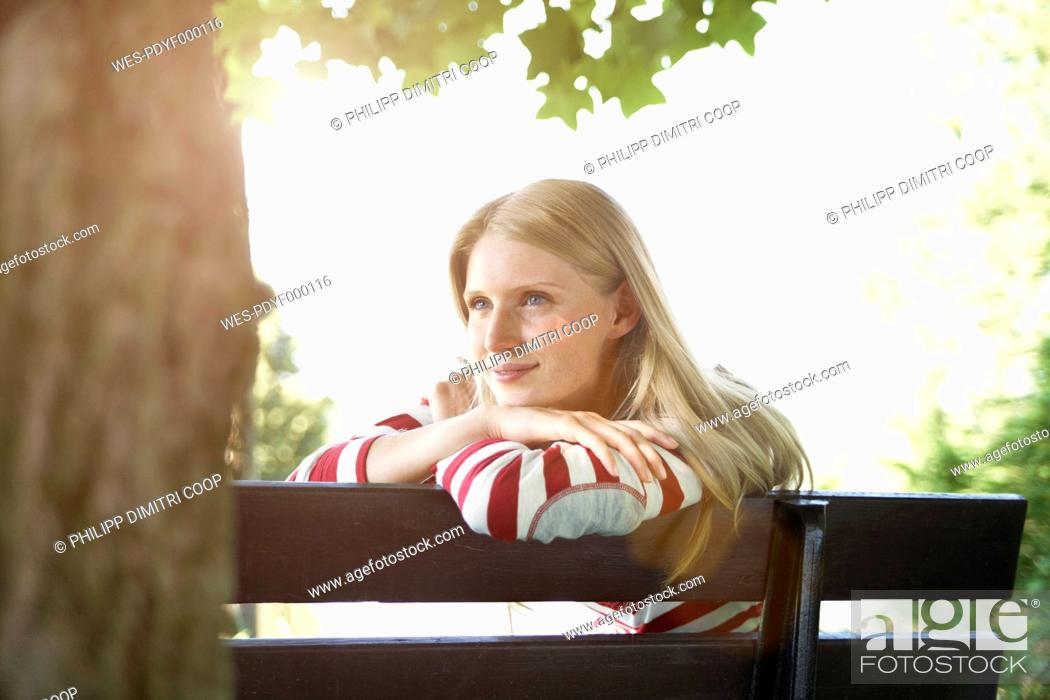 Stock Photo: Germany, Cologne, Young woman sitting on park bench, smiling.