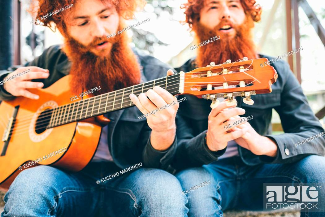 Imagen: Young male hipster twins with red beards sitting playing guitar.