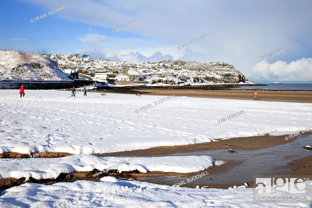 Stock Photo: Benllech, Isle of Anglesey, North Wales, UK, Europe  People walking on the beach with snow in winter.