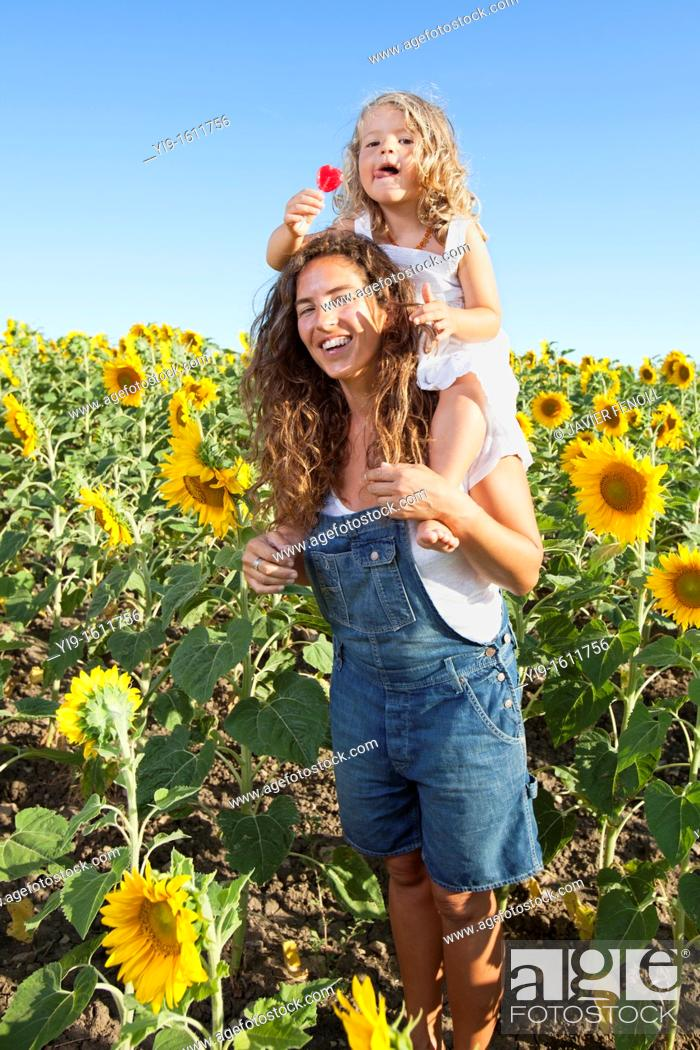 Stock Photo: mother and daughter in a field of sunflowers.