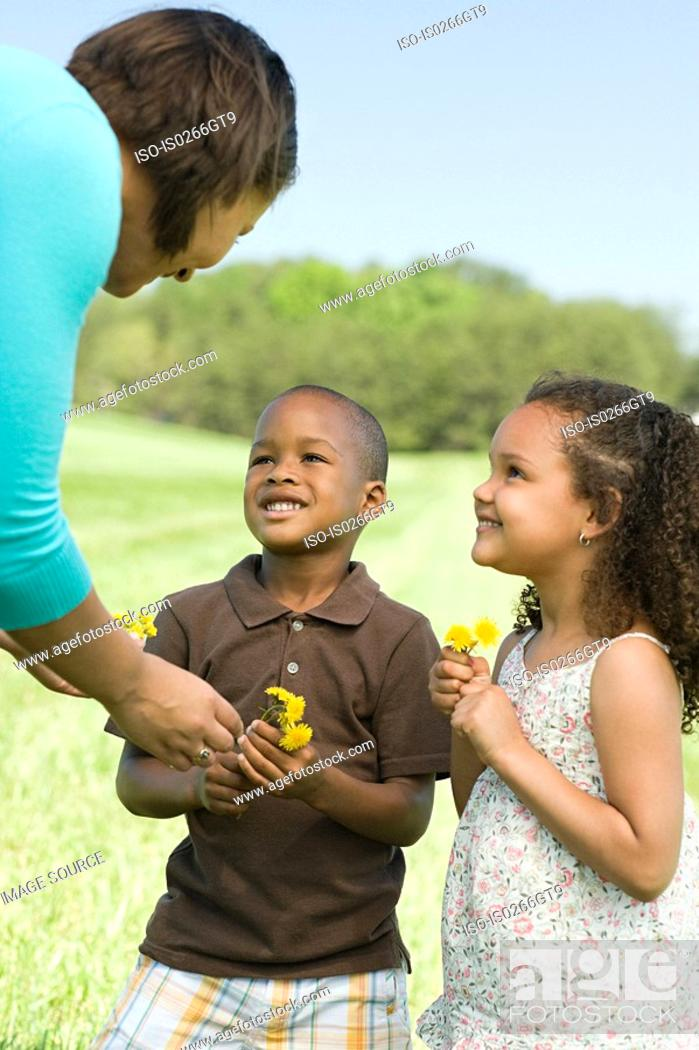 Stock Photo: Mother and children with flowers.