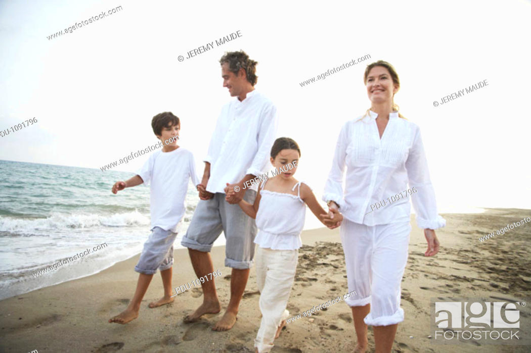 Stock Photo: Family walking on beach, son and daughter (7-9) holding parents' hands.