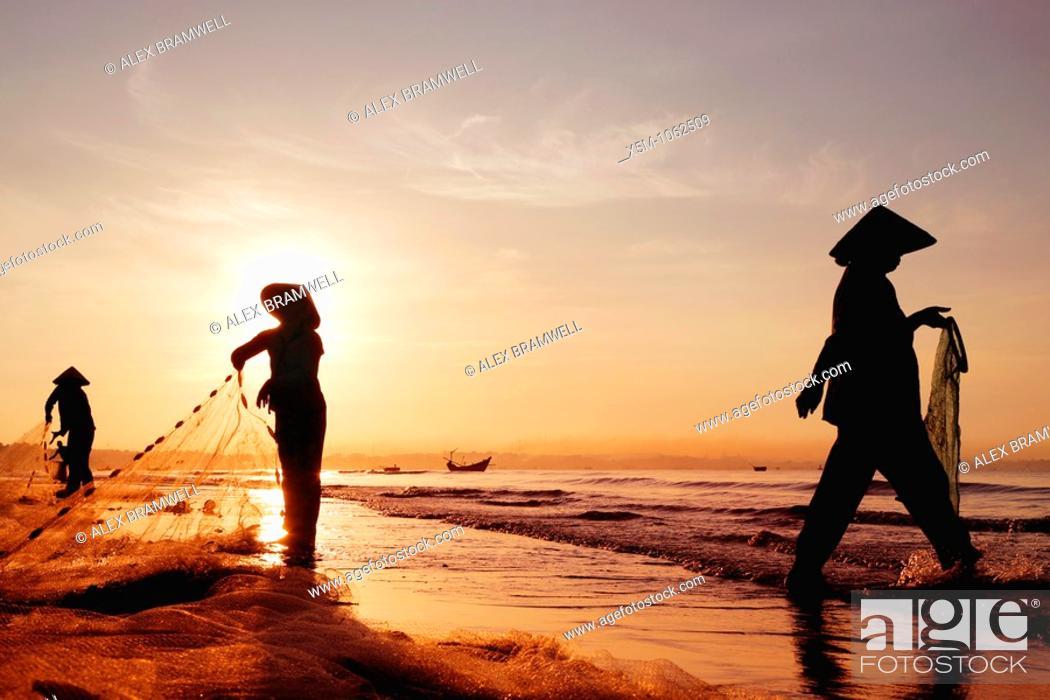 Stock Photo: Three women in traditional hats on Mui Ne Beach, Vietnam  Fishing at sunrise.