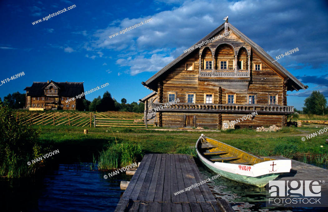 Stock Photo: Traditional Russian wooden houses (early 191th- 20th century), pier and boat, Vasilevo. Kizhi island, Onega lake, Karelia, Russia.