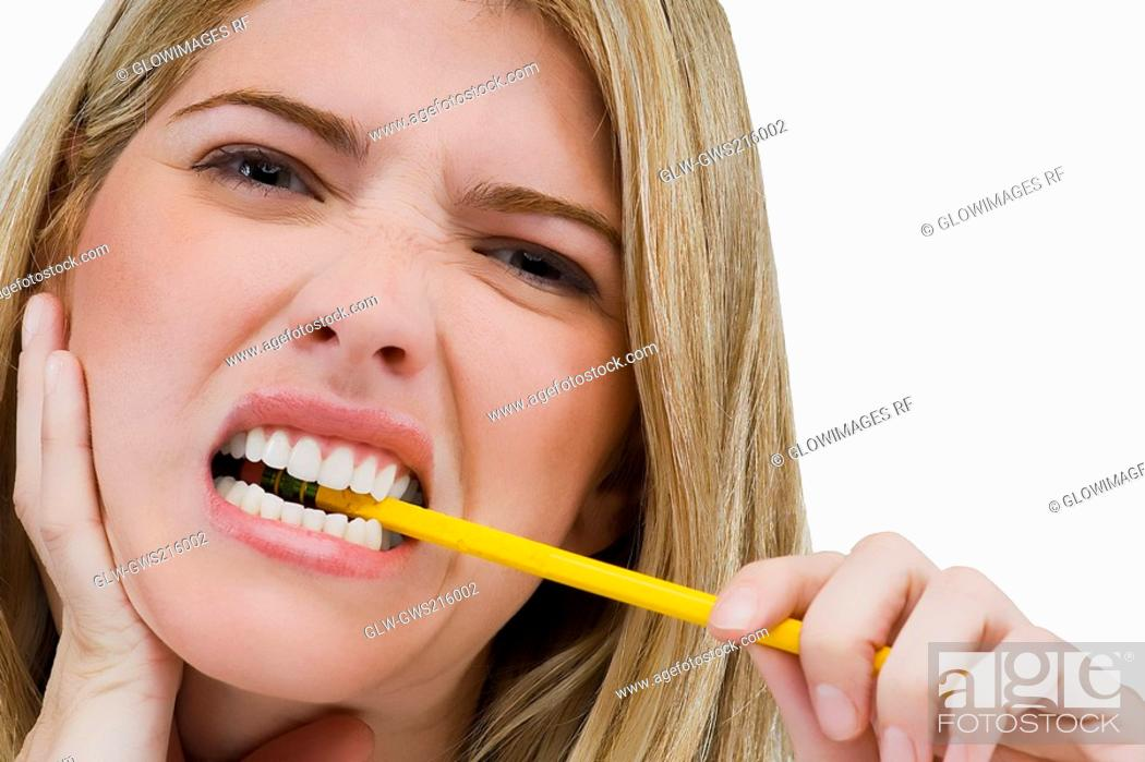 Stock Photo: Portrait of a young woman biting a pencil.
