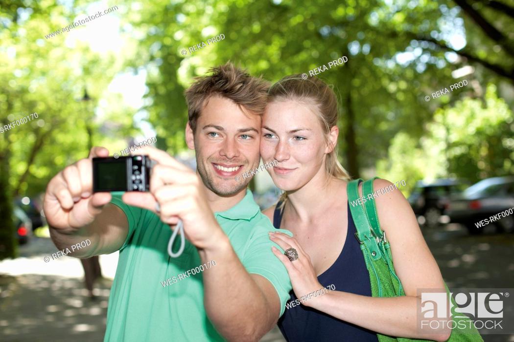 Stock Photo: Germany, North Rhine Westphalia, Duesseldorf, Couple taking photo of themselves, smiling.