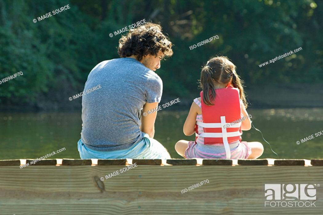Stock Photo: Father and daughter on jetty in lake.
