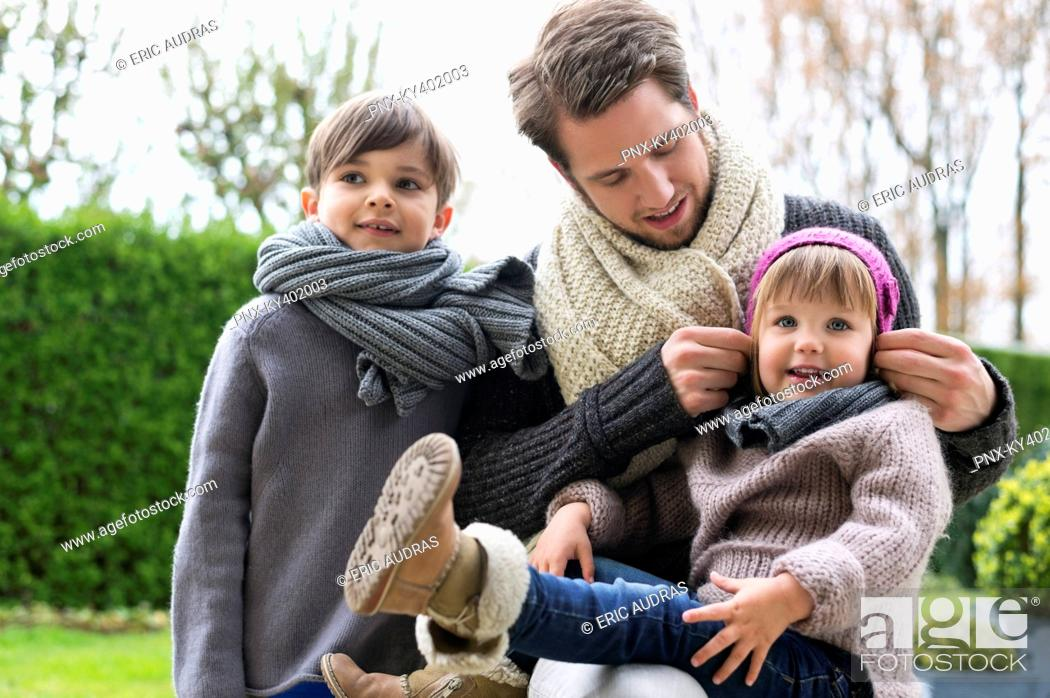 Stock Photo: Man with his son and daughter in warm clothing in a park.