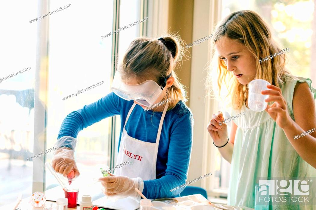 Stock Photo: Two girls doing science experiment, with red liquid.
