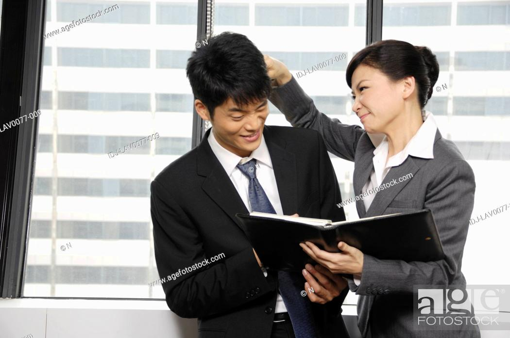Photo de stock: Businesswoman discussing a report with her colleague.