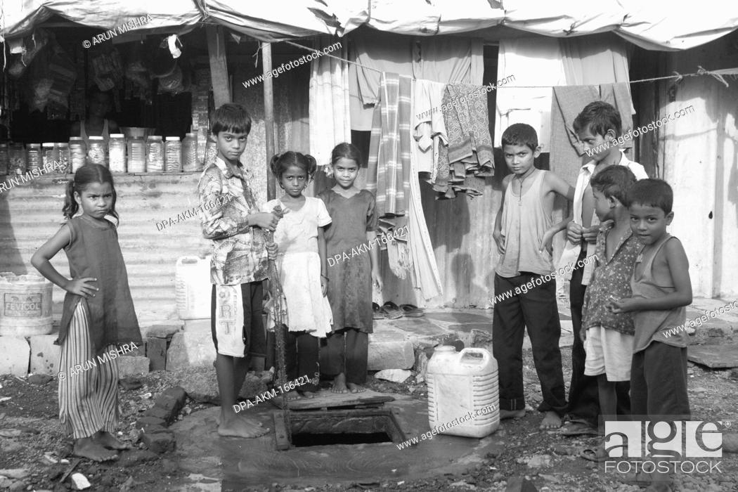 Stock Photo: Children stand front of bore well in Malvani slum ; Malad ; Bombay Mumbai ; Maharashtra ; India.