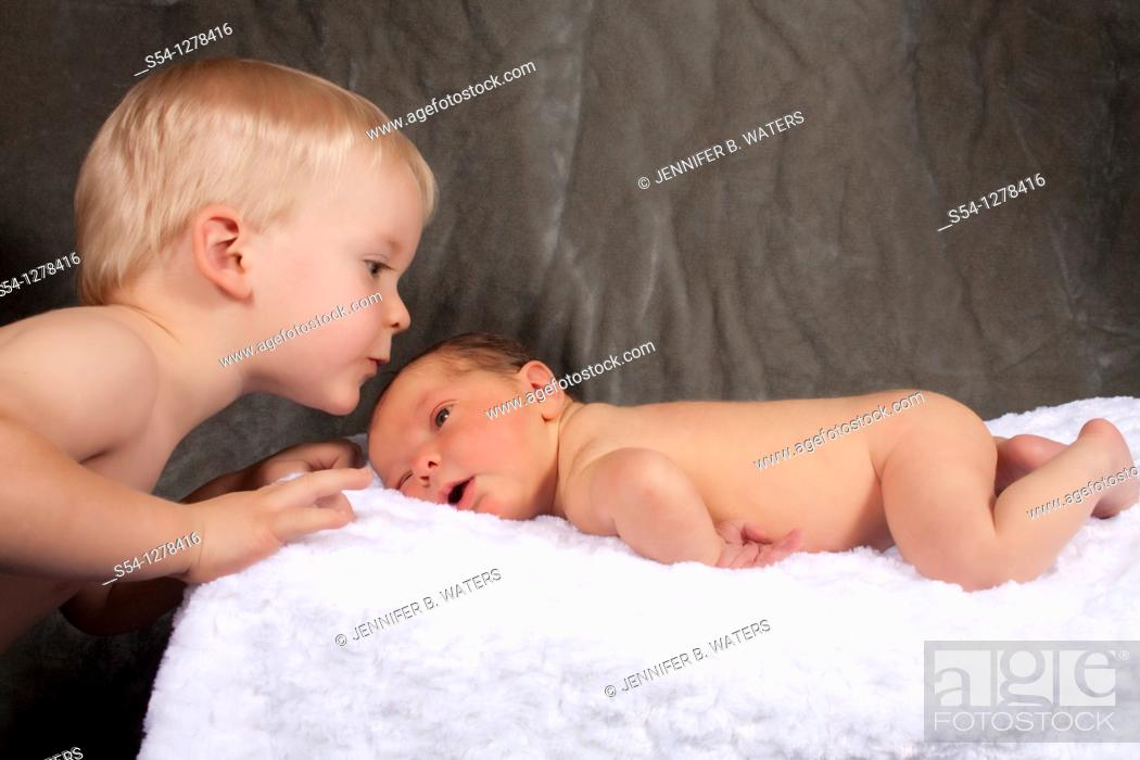 Stock Photo: A two year old boy kisses his newborn baby brother.