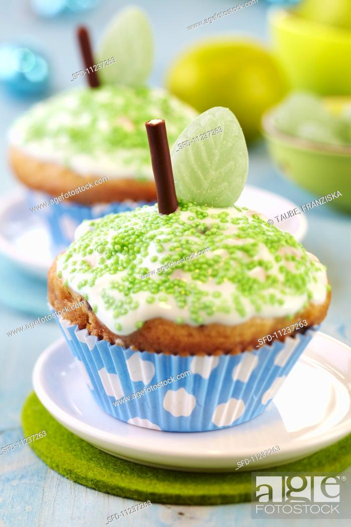 Stock Photo: Apple muffins decorated as apples with icing, green sprinkles, chocolate sticks and leaf-shaped sweets.