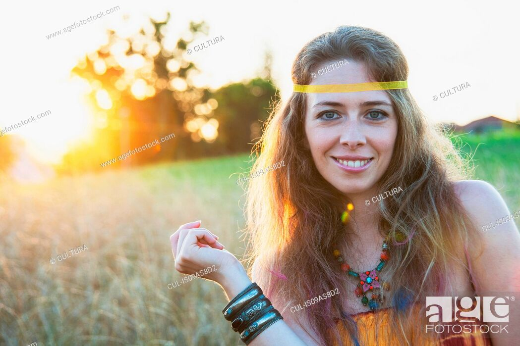 Imagen: Portrait of mid adult woman wearing hippy clothes, standing in field at sunset, smiling.
